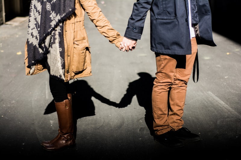 White couple holding hands but facing away from each other