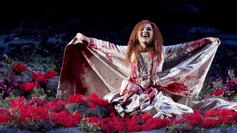 Elena Mosuc as Lucia at Teatro Regio (Turin), directed by  Damiano Michieletto.   Lucia kneels on the ground in a bloody wedding gown. She is surrounded by red flowers.