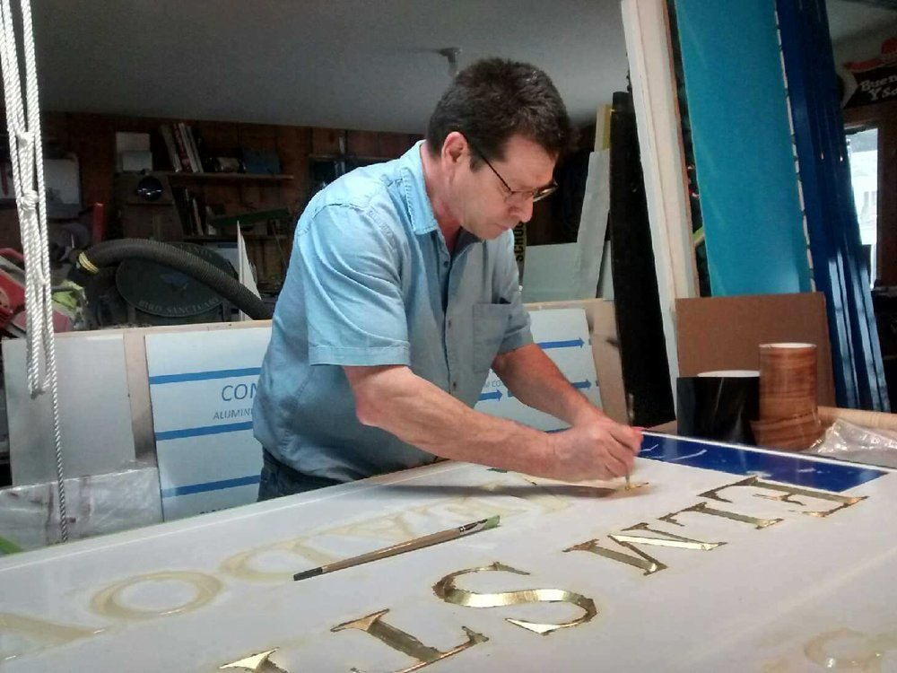 Bob Godfrey guilding a hand-carved wooden sign. Photo taken by Ilse Godfrey