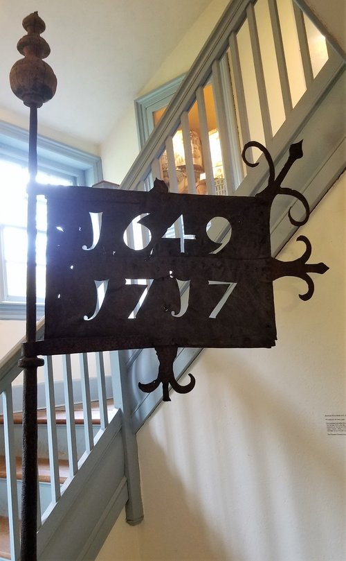 1717 Church banner weathervane on display at Clinton Academy.  One of only 2 church banner weathervanes surviving in New York State. It is made from hand wrought iron and cut copper.  The unusually numbering is similar to the script used in 18th century handwriting. 1649 signifies the year the first church was built, a year after the settlement of East Hampton.  1717 signifying the year the second church was built.  The large wooden ball that supported the weathervane, originally covered in copper and gold plate still survives at the base of the weathervane.