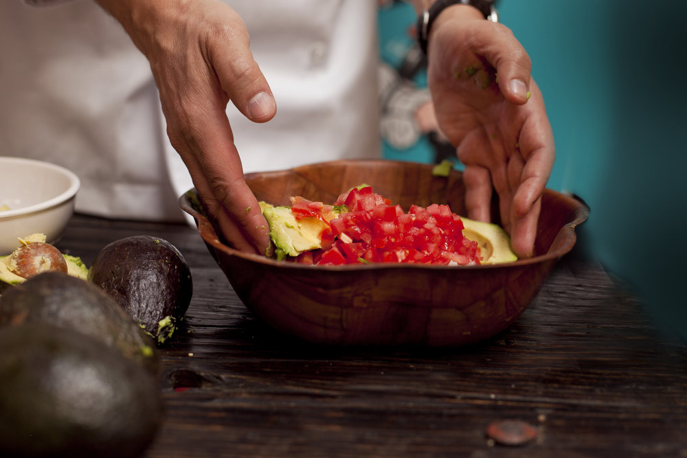 Mixing guacamole in a bowl.