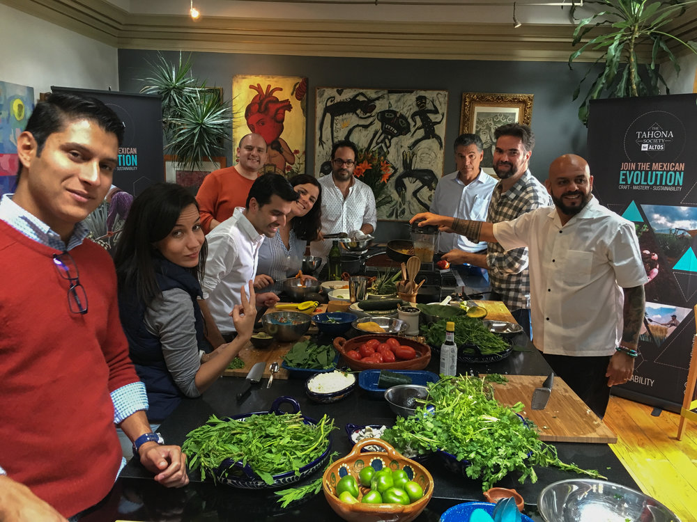 Group of nine people cooking Mexican food at a corporate event at Casa Jacaranda.