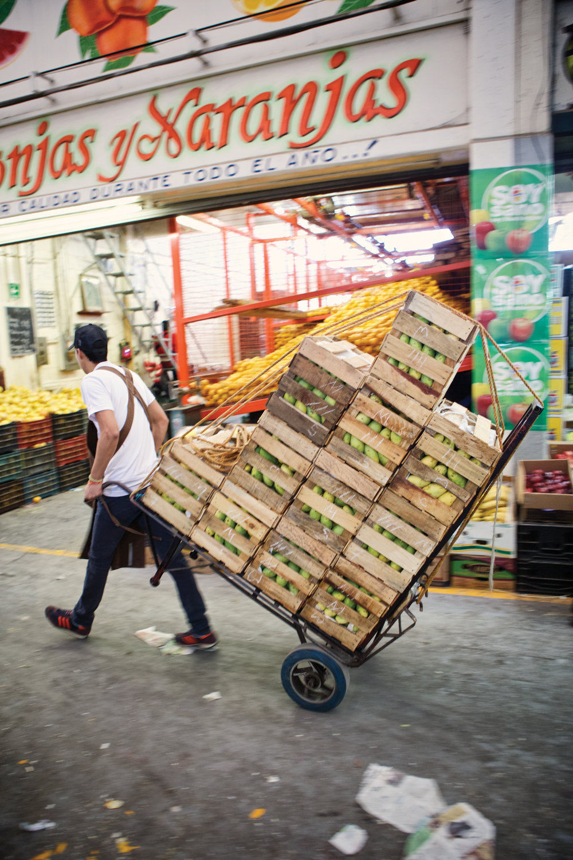 man carries cart of crates full of mangos