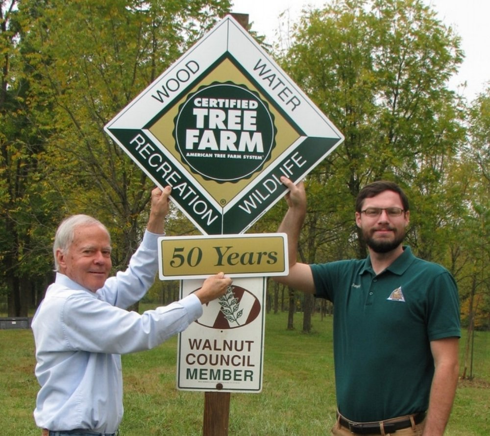 Mike Trial receiving 50-year tree farm sign.
