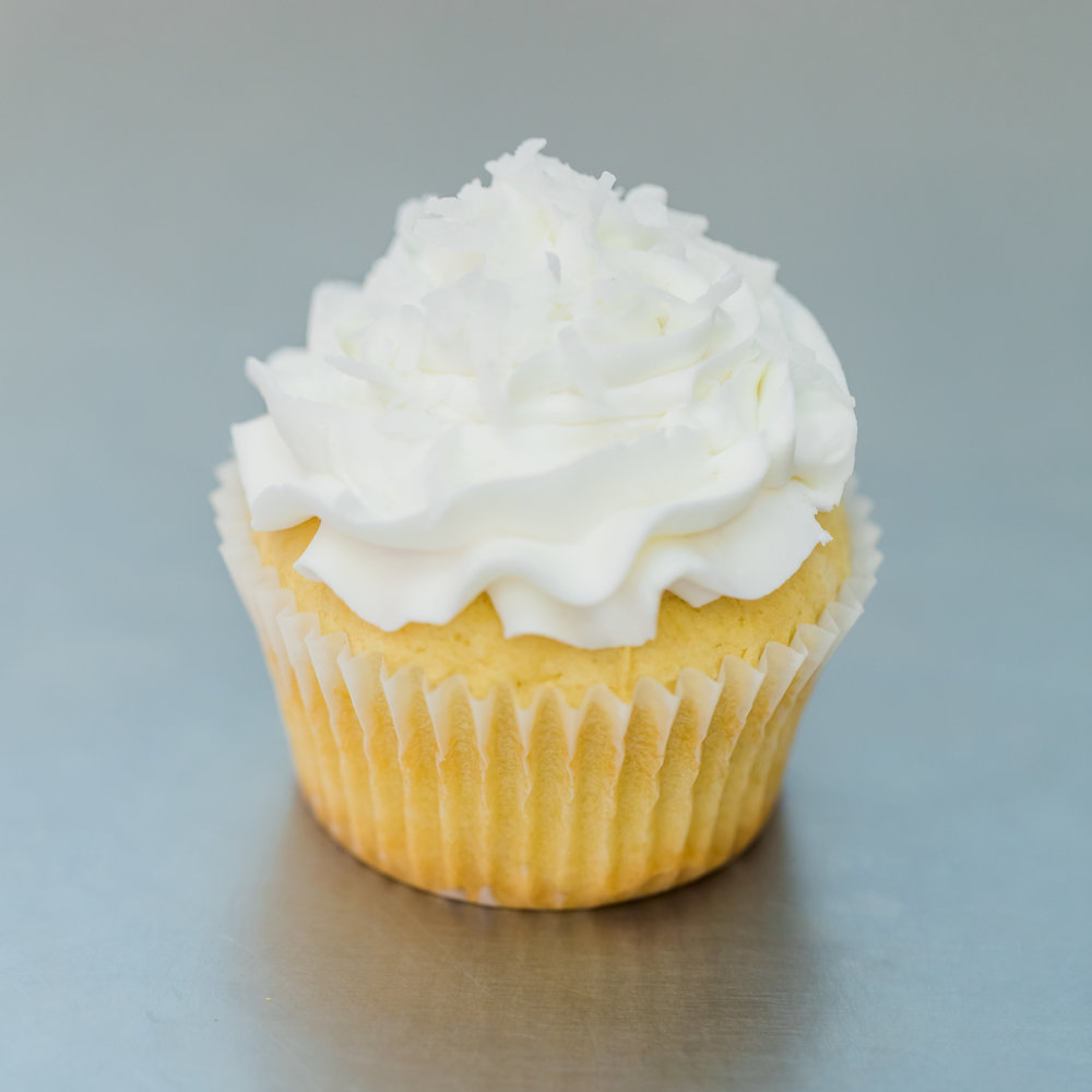 Coconut Lopez - Vanilla cake filled with cream of coconut, frosted with whipped cream and topped with shredded coconut
