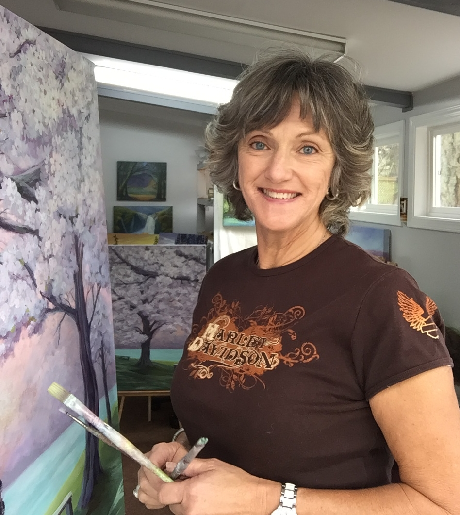 Artist Marilyn Peeters painting a painting in her studio. Painting features purple trees near the ocean, based in the Comox Valley on Vancouver Island in British Columbia.