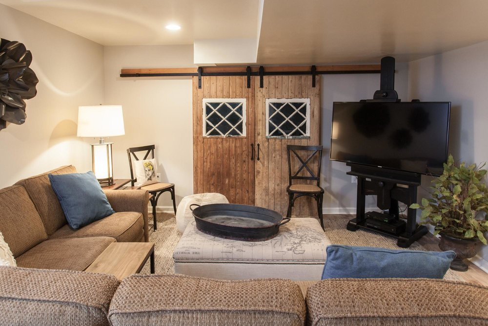 Large sectional sofa with sliding wood barn doors against the wall