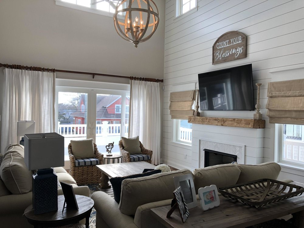 Living room with shiplap walls, sofa, and lamps