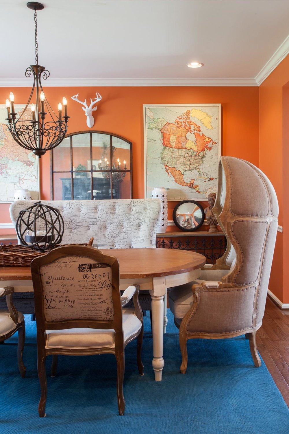 Dining room with orange painted walls and hanging maps