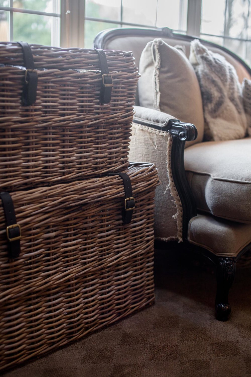 Stacked wicker chests next to beige colored love seat