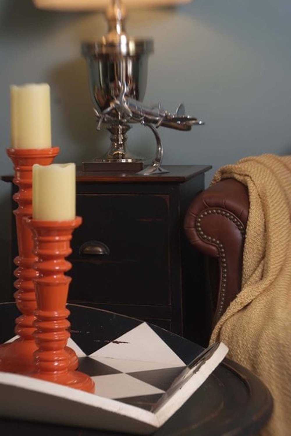Tall orange candle stick holders with brown leather sofa in background