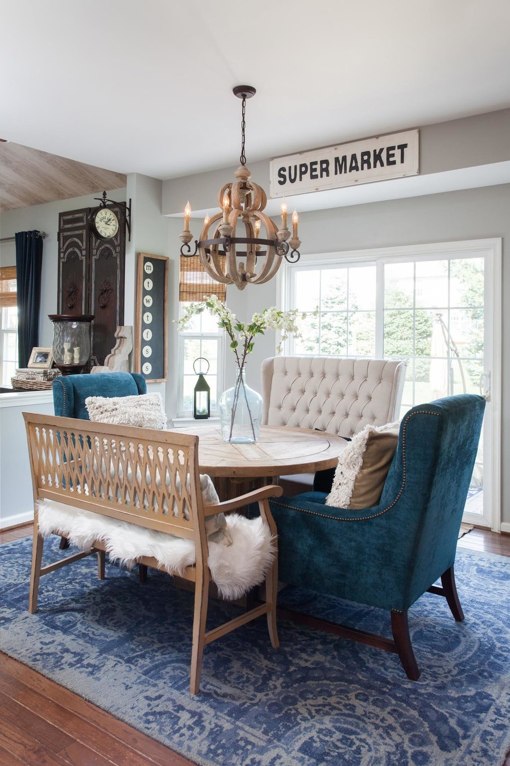 Bright breakfast nook with round wooden table and hanging wooden light fixture