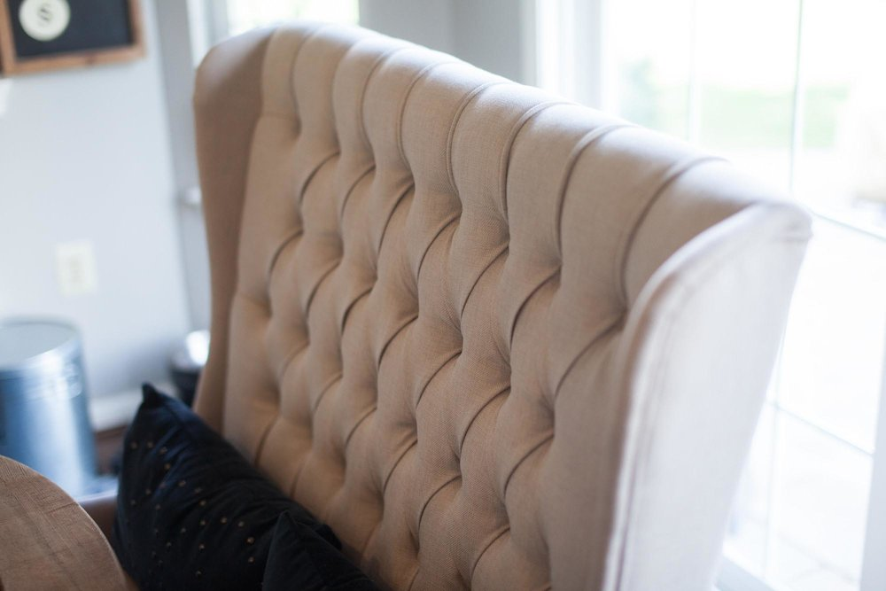 Beige colored stuffed chair with blue pillow