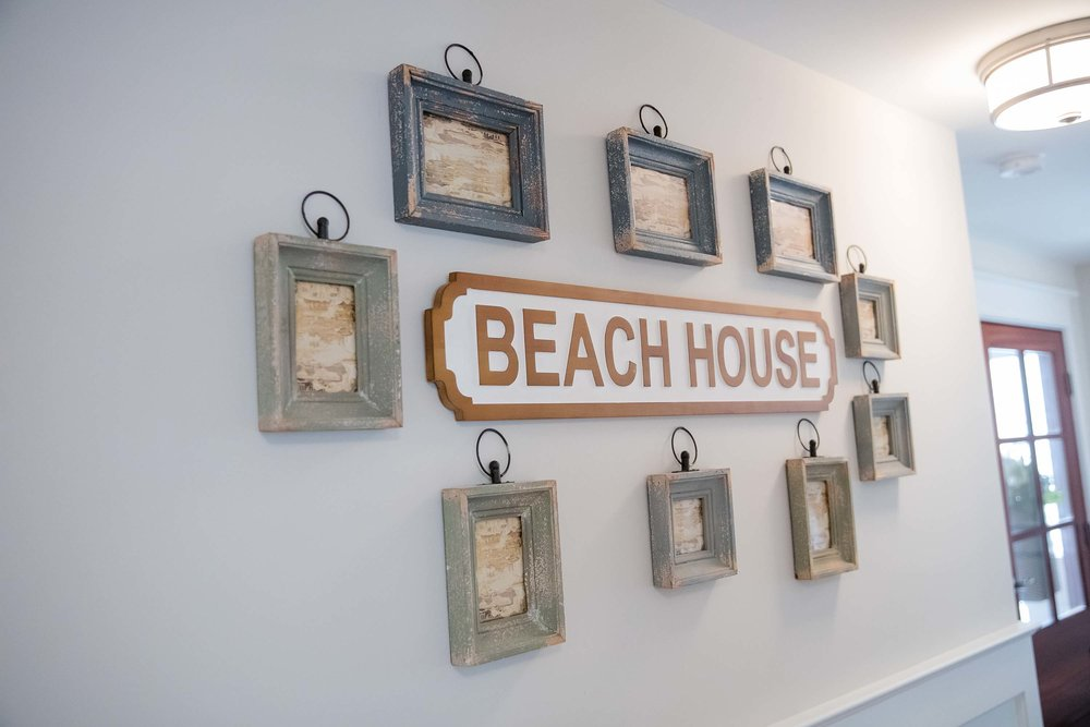 Coastal style wooden picture frames hanging on wall and wooden beach house art
