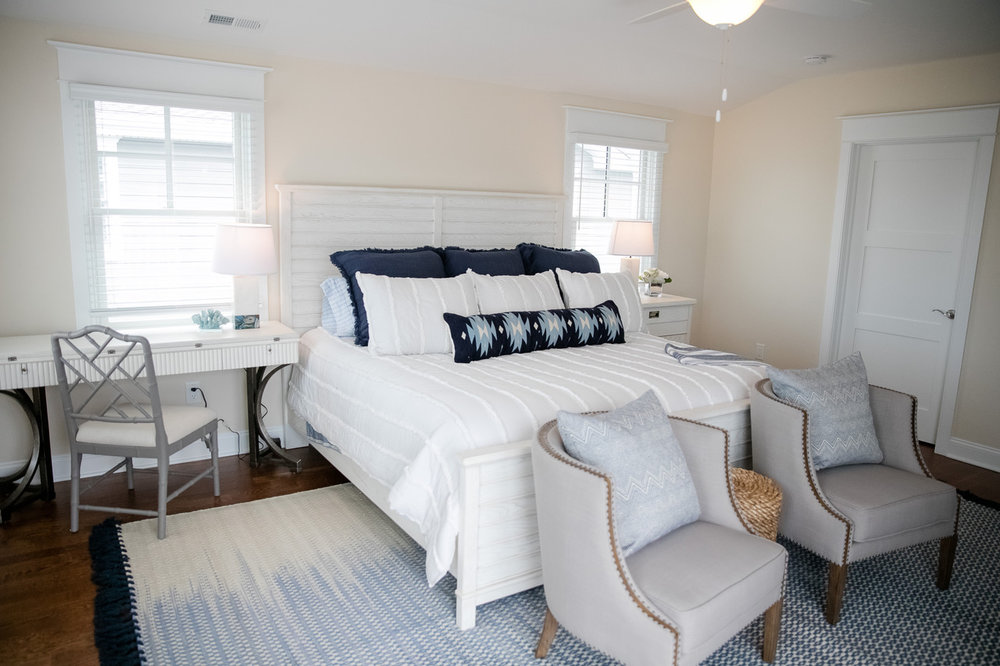 Bright bedroom with white bed and two sitting chairs