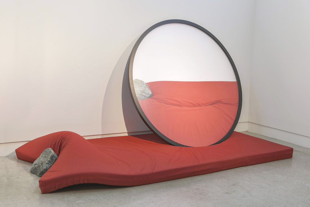 Hirofumi Isoya,  Parallax Gesture,  2015,   Frame 115 cm in diameter, 3 cm thick, Mattress 30 × 60 × 90 cm, Rock 20 × 20 × 25 cm. Courtesy of the artist and the Mori Art Museum