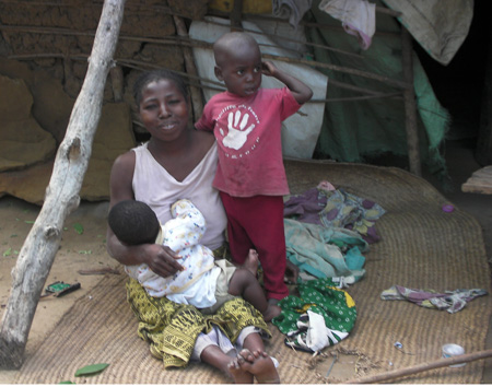 Saidi's mum with Saidi and his baby brother outside their house. The mat they are sitting on was used as a bed for mum and the five children.