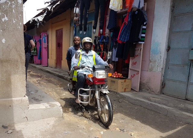 A Boda Boda taking a passenger past a row of shops