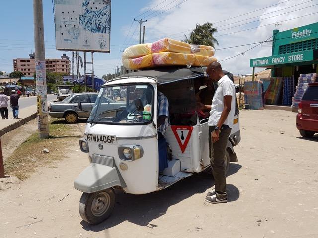 A Tuk Tuk carrying passengers and a matress