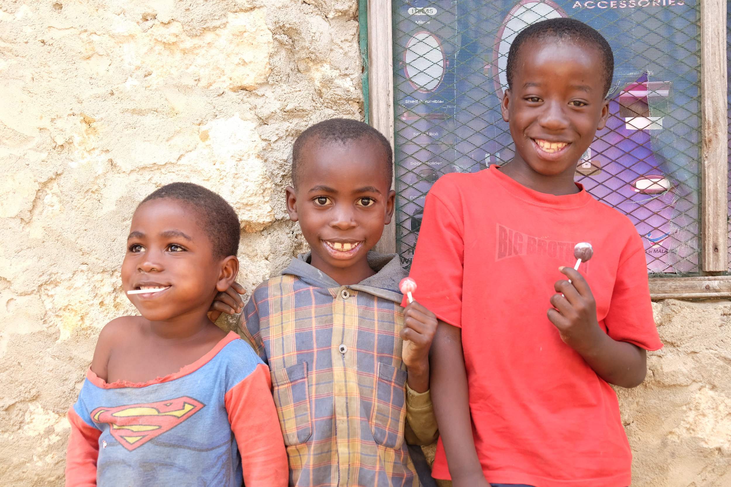 So big now! Saidi (centre) and Steven (right) outside their house in October 2016. The other cutie is Simon, Saidi's baby brother!