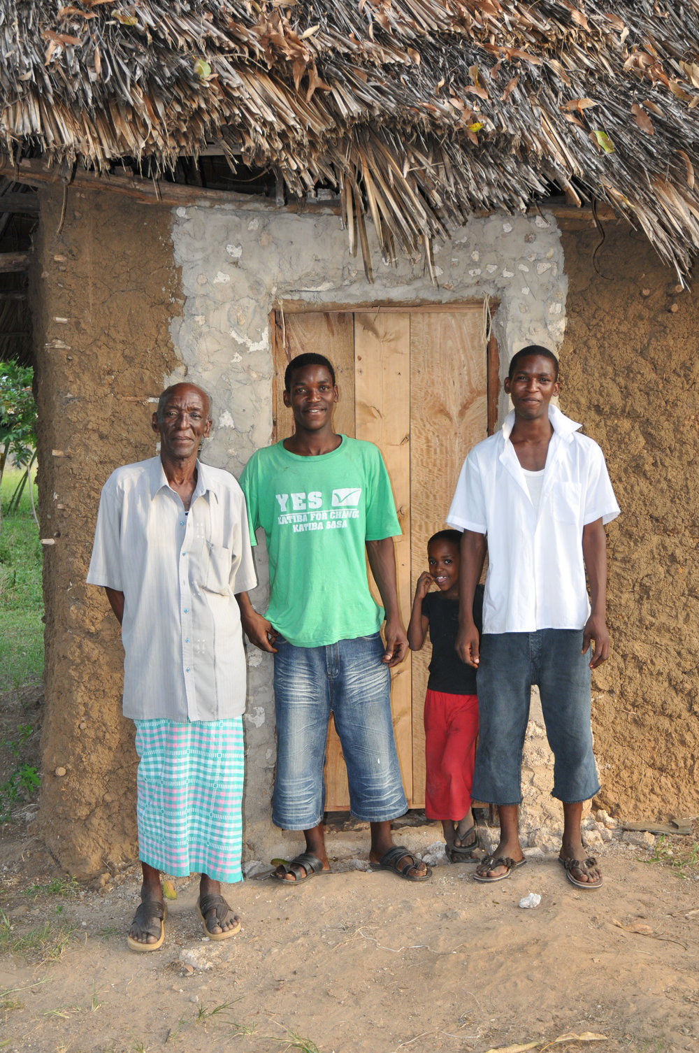 Built his own house - Emmanuel (on the right) with his father, brother and little sister outside his house.