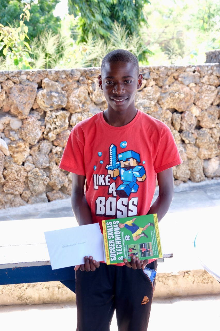 Emmanuel with his gift and letters from his sponsors