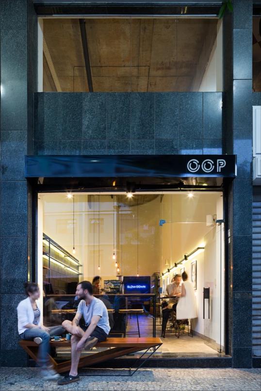 OPP Café, por Paulo Augusto Campos e Marina Garcia.  Neste caso, optou-se pelo uso da cor preta para a coerência com o granito existente da fachada do edifício e destaque do nome do café. Além disso o uso do banco na porta convida os pedestres a sentarem.