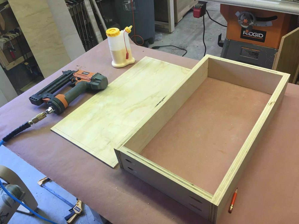 Supplies needed, a nailer, the bottom drawer plywood panel and glue.