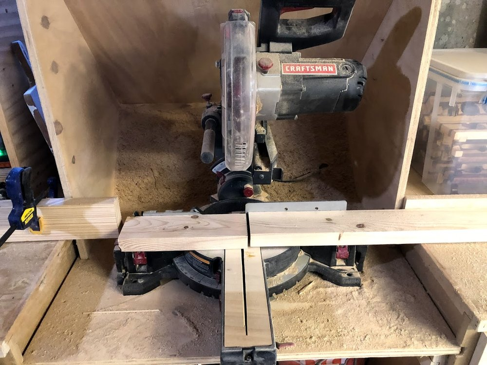 """Here you can see my very dusty miter saw with a stop block set up to the left of the blade to make sure all my cuts were 10-1/2"""" long."""
