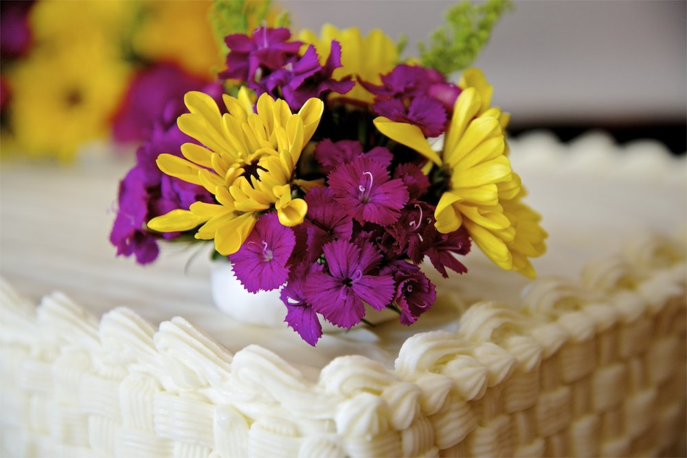 Fresh flowers atop a large sheet cake