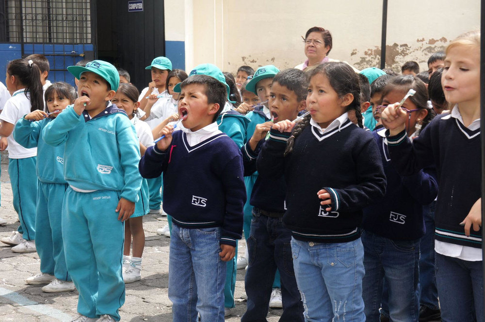 Ecuadorian students using their new toothbrushes