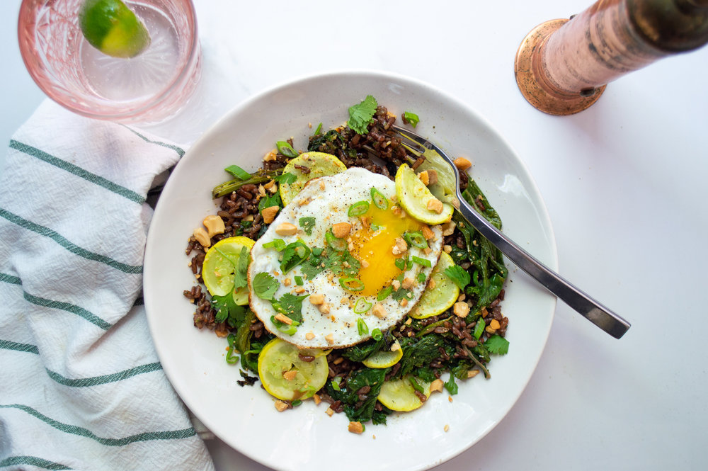 Red rice with leftover stir-fried greens, sauteed summer squash, and a fried egg, topped with scallions, cilantro and crushed cashews.