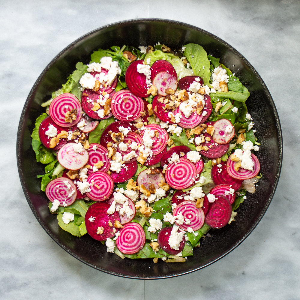 raw beet and feta salad with lettuce and beet greens