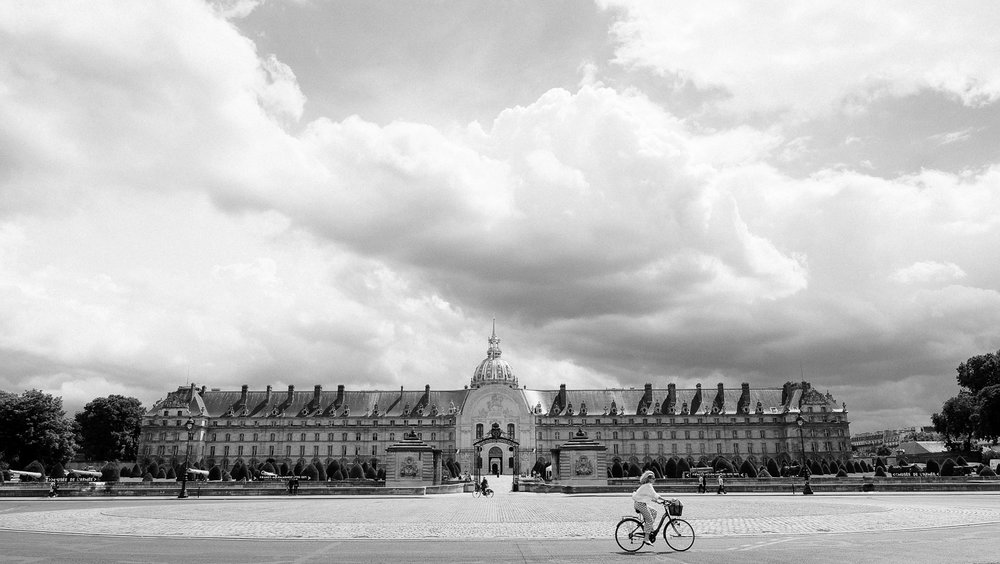 Woman rides her bike in front of Les Invalides