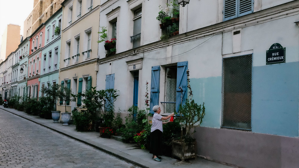 A lady waters her plants on Rue Crémieux