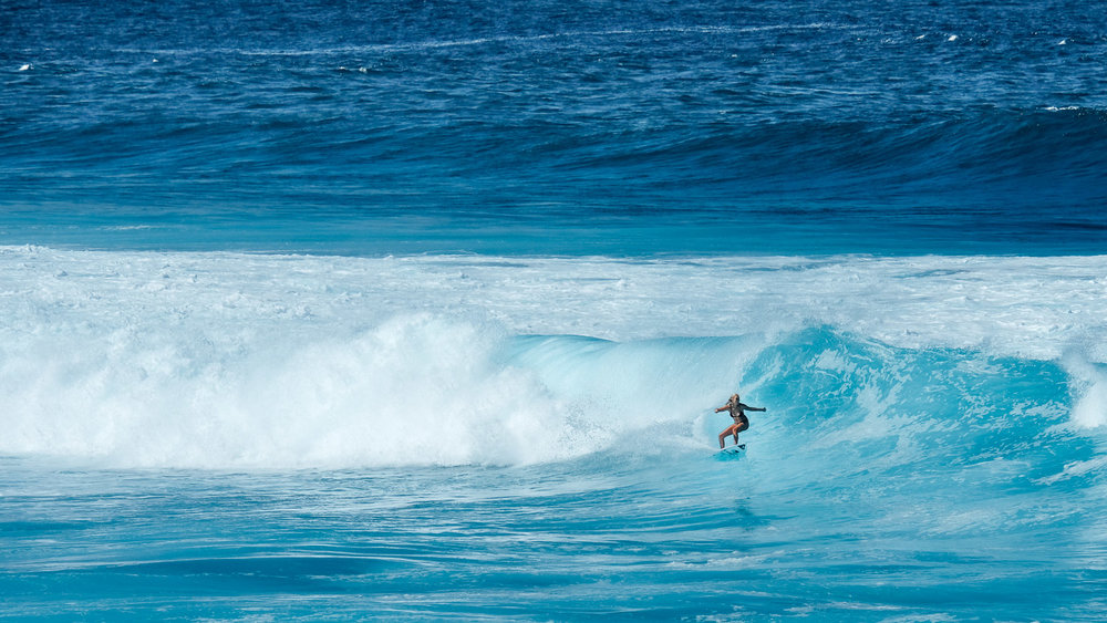 A woman surfing at Ho'okipa Beach