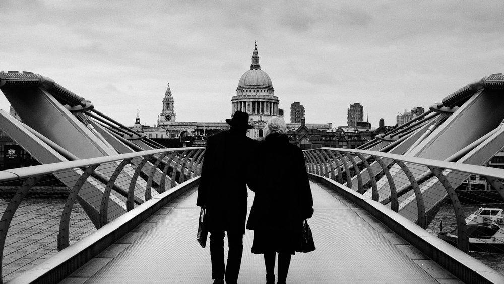 A couple walking over Millennium Bridge