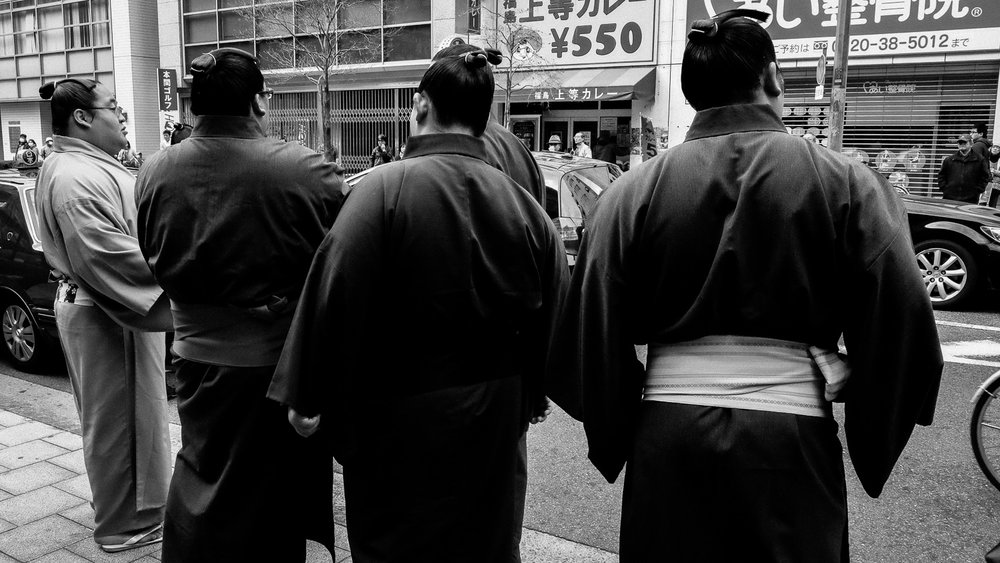 Sumo wrestlers waiting outside the tournament arena
