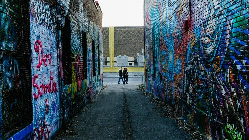 People walking through Graffiti Alley