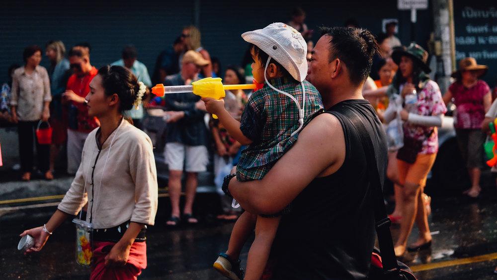 A little boy fires his water gun during Songkran