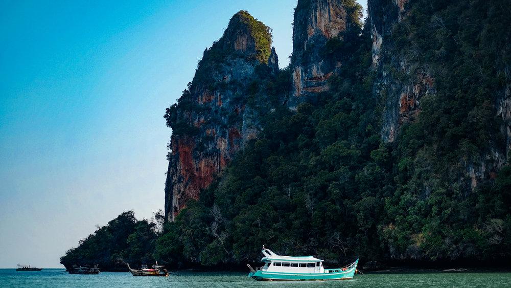 A boat by the limestone cliffs in Krabi