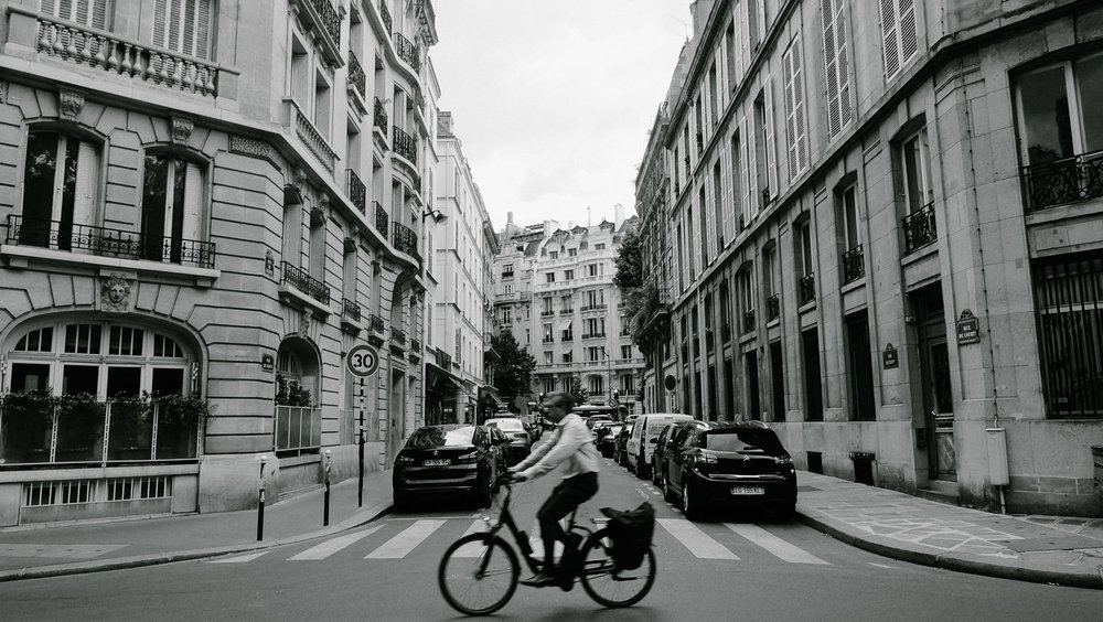 """A man rides his bike through the streets of Paris. Travel photography and guide by © Natasha Lequepeys for """"And Then I Met Yoko"""". #paris #paristravel #photoblog #travelguide #france #parisitinerary #parishighlights #parissights #travelblog #travelphotography #landscapephotography #travelitinerary #fujifilm #paristravelguide #architecturephotography #europe #travelblogger #wanderlust #explore #travel"""
