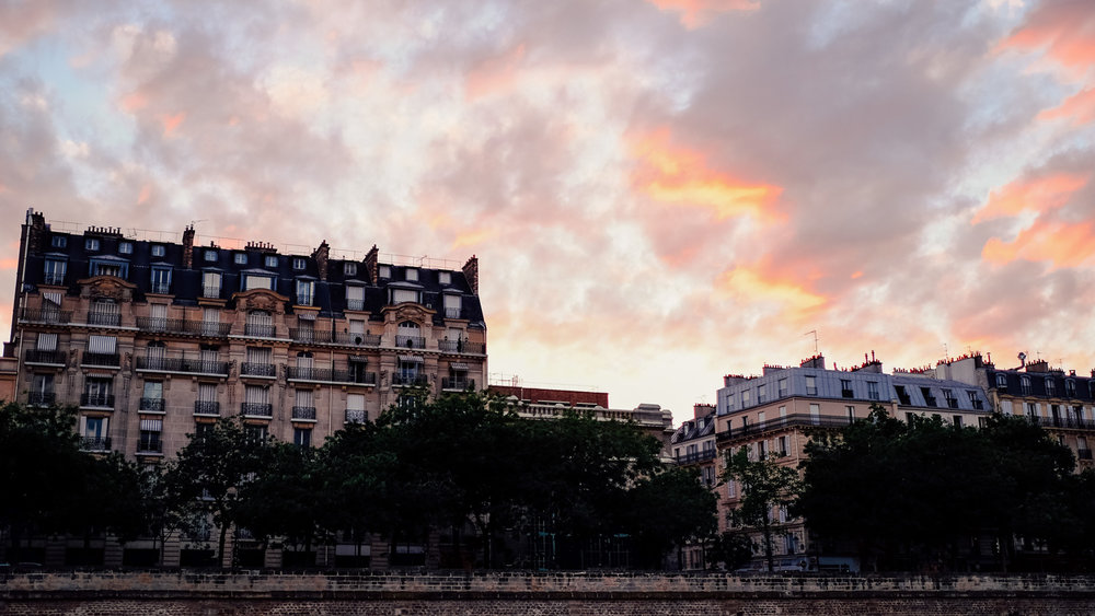"""A beautiful sunset over some buildings in Paris. Travel photography and guide by © Natasha Lequepeys for """"And Then I Met Yoko"""". #paris #paristravel #photoblog #travelguide #france #parisitinerary #parishighlights #parissights #travelblog #travelphotography #landscapephotography #travelitinerary #fujifilm #paristravelguide #architecturephotography #europe #travelblogger #wanderlust #explore #travel"""