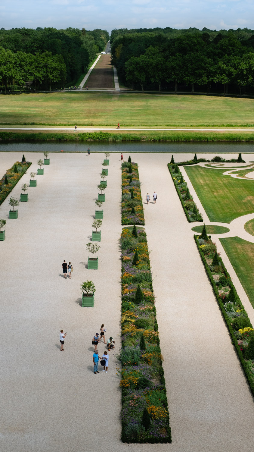People walking through the French gardens of Chambord