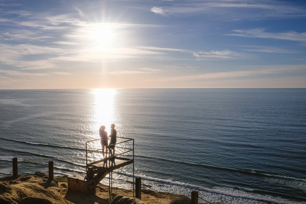 "A couple enjoying the sunset at Torrey Pines Gliderport - San Diego travel guide by ""And Then I Met Yoko"". Photography by Natasha Lequepeys #travelphotography #travelblog #sandiego"