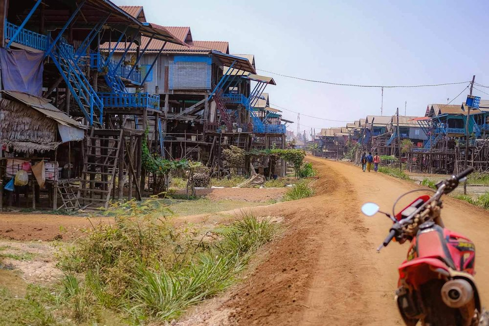 A dusty road in the village of stilt houses