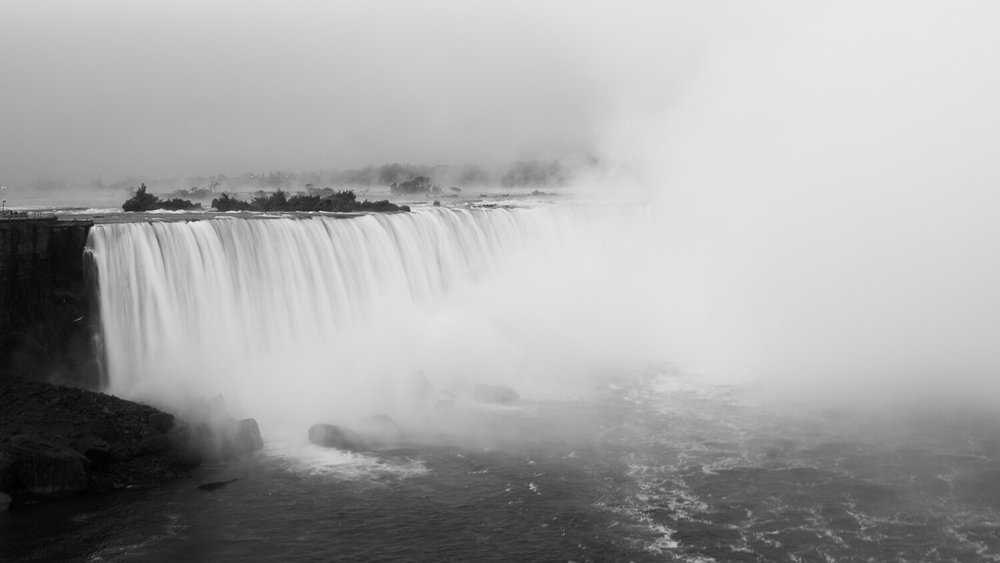 "Horseshoe Falls on a misty morning, Niagara Falls Canada. Travel photography and guide by © Natasha Lequepeys for ""And Then I Met Yoko"". #niagara #horseshoefalls #ontario #canada #discoverontario #niagarafalls #travelguide #photoblog #travelblog #travelphotography #blackandwhite #travelitinerary #fujifilm #waterfall #bnwphotography #nature #notl #travelblogger #niagaraitinerary #niagaraphotography"