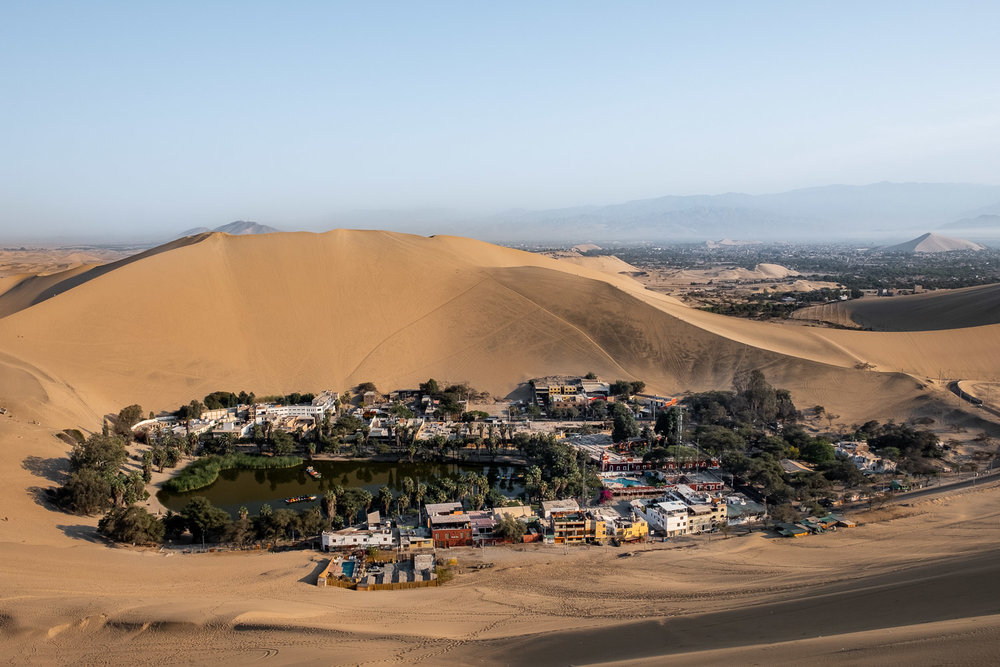 """The oasis town of Huacachina from the top of a sand dune, Peru. Travel photography and guide by © Natasha Lequepeys for """"And Then I Met Yoko"""". #peru #ica #huacachina #photoblog #travelblog #travelphotography #landscapephotography #travelitinerary #fujifilm #sanddunes #desert #sunset #sandboarding #streetfood #foodphotography #oasis #backpacker #winery #travel #huacachinatours"""