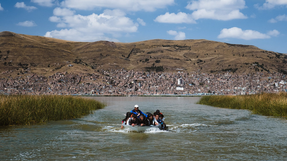 """Locals on their boat, leaving Puno. Travel photography and guide by © Natasha Lequepeys for """"And Then I Met Yoko"""". #peru #laketiticaca #amantani #taquile #homestay #culturalexperience #photoblog #travelblog #travelphotography #fujifilm #travel #travelperu #southamerica #allwaystravel #laketiticacaitinerary #puno #uros #floatingislands #pachamama #pachatata"""