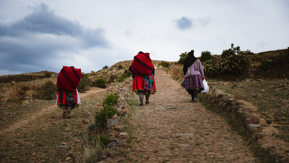 """Women carrying their products to sell on Amantani Island. Travel photography and guide by © Natasha Lequepeys for """"And Then I Met Yoko"""". #peru #laketiticaca #amantani #taquile #homestay #culturalexperience #photoblog #travelblog #travelphotography #fujifilm #travel #travelperu #southamerica #allwaystravel #laketiticacaitinerary #puno #uros #floatingislands #pachamama #pachatata"""